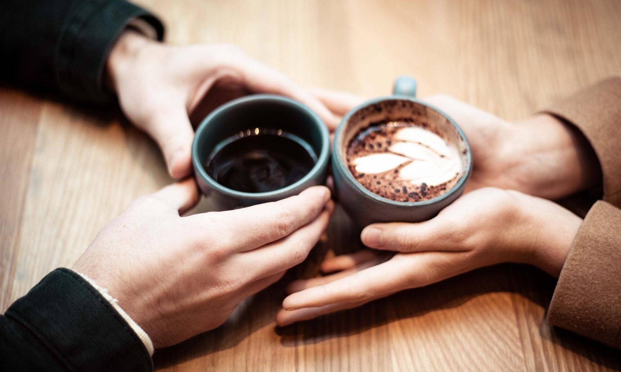 Herrenhände und Frauenhände umfassen Kaffeetassen beim date